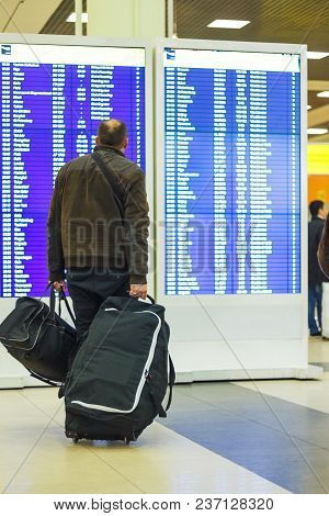 Passenger With Luggage Looking At Timetable Arrival Or Departure Board In Airport