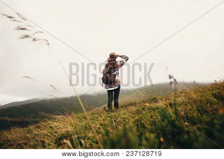Stylish Traveler Girl Holding Hat With Backpack And Windy Hair In Mountains Clouds. Summer Vacation.