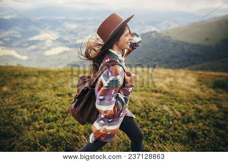 Travel And Wanderlust Concept. Stylish Traveler Hipster Girl Holding Hat, With Backpack And Windy Ha