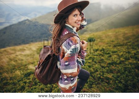Happy Traveler Hipster Girl In Hat, Walking With Backpack And Smiling In Windy Mountains In Clouds.
