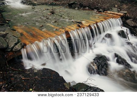 Beautiful Waterfall Cascads On River In Forest In Mountains. Wooden River Dam With Water Motion. Bea
