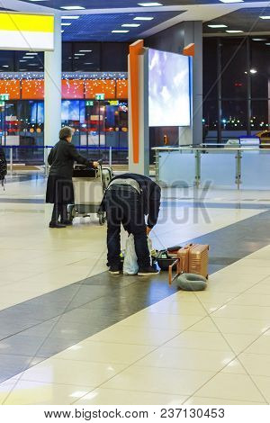 Young Man Shift Things Out Of A Suitcase In Terminal Hall Airport