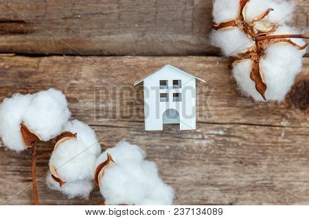 Miniature White Toy House With Cotton Flowers On A Rustic Old Vintage Wooden Background, Free Space