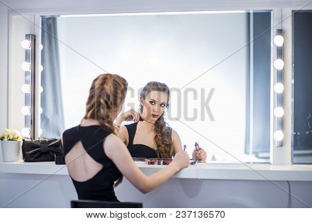 Beautiful Girl Sitting At The Table Make-up Artist Near The Mirror