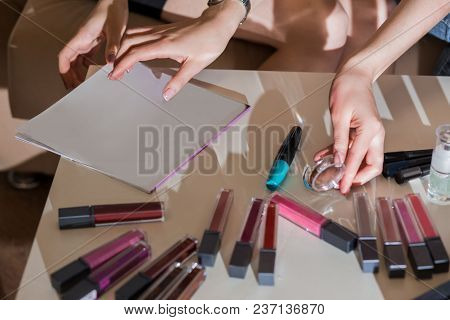 Cosmetics On The White Coffee Table, Lipstick, Lip Gloss, Mascara, Eyeshadow, Magazine, Hands Of Gir