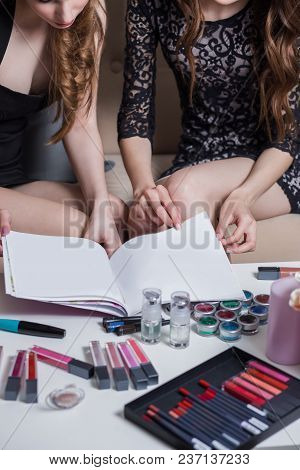 Two Girls Flipping Magazine, Catalog Cosmetics For A Coffee Table, A Lot Of Lipsticks, Lip Pencils,