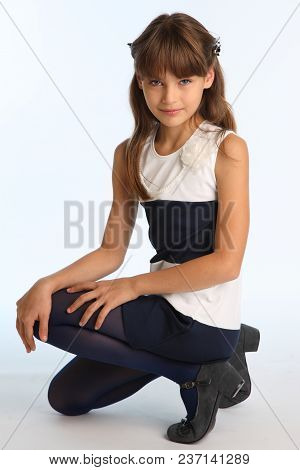 Slender Beautiful Girl In A Striped Dress Sat On Her Knee. Pretty Happy Attractive Child In Blue Tig