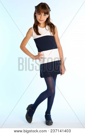 Beautiful Girl In A Striped Dress Is Standing At Full Length. Elegant Attractive Child With A Slende