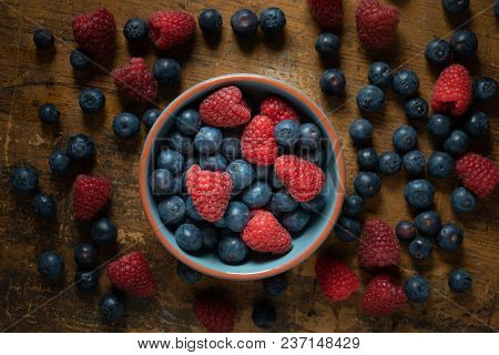 Raspberries And Blueberries In A Blue Bowl On A Rustique Table