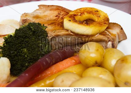 Pork Chop A Pork Chop Served With Vegetables And An Apple Ring