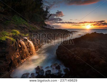 Setting Sun At Sunset Illuminates A Small Waterfall Falling Into The Ocean With The Na Pali Coastlin