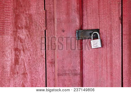 The Rusty Steel Key Locking On The Hinge Of The Red Wooden Door