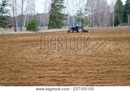 The Tractor Sows Crops, Performs Agrarian, Agricultural, Farming, Work On The Field, Land.