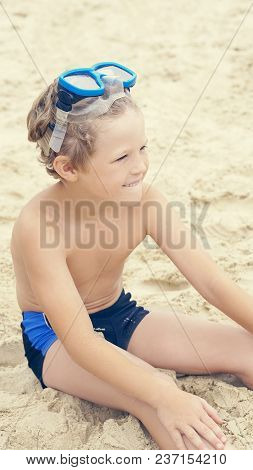 Little Boy With Snorkeling Equipment Sitting On Sand On Tropical Beach And Looking Into The Distance