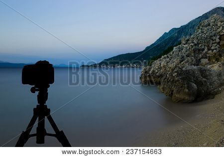 Camera On Tripod With Sunset Over The Sea In Background / Podgora, Croatia