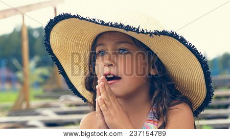 Beautiful Little Latin Girl In A Hat On The Seashore Folded Her Hands In Prayer And Looks Into The D