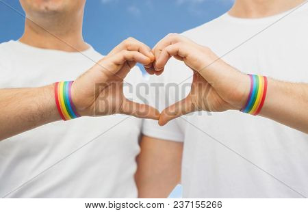 lgbt, same-sex love and homosexual relationships concept - close up of happy male couple wearing gay pride rainbow awareness wristbands showing hand heart gesture