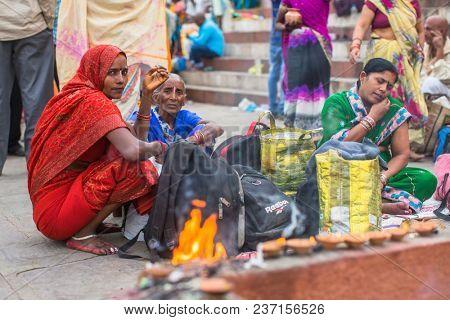 VARANASI, INDIA - MAR 15, 2018: Pilgrims expect ritual  Agni Pooja (Sanskrit: Worship of Fire) on Dashashwamedh Ghat - main and oldest ghat of Varanasi located on the Ganges.
