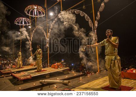 VARANASI, INDIA - MAR 15, 2018: A group of priests perform Agni Pooja (Sanskrit: Worship of Fire) on Dashashwamedh Ghat - main and oldest ghat of Varanasi located on the Ganges.