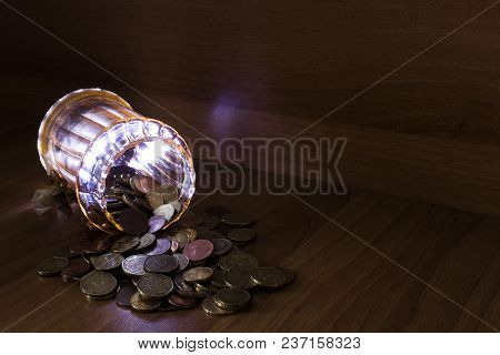 Jar Of Glass Full Of Euro Coins On A Table Using Light Painting Technique Composition