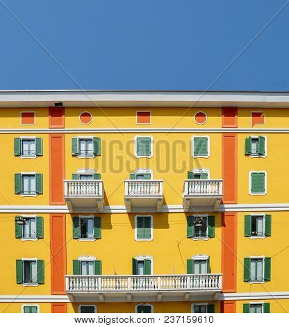 Daylight View To Vibrant Mediterranean Colorful Yellow Building Facade In Milan, Lombardy, Italy