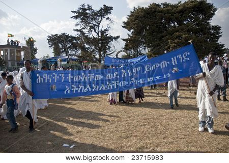 Christian Orthodox Devotees Carrying A Banner With Amharic Writing On It At The Timket Festival.