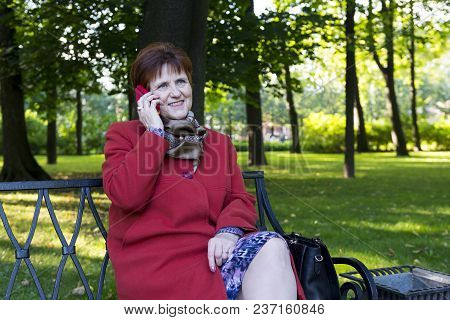 Adult Woman In Red Coat In The Park Talking On The Phone