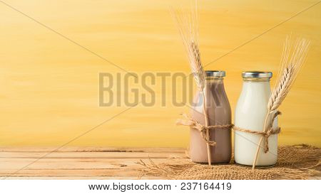 Milk And Chocolate Milk Bottles On Wooden Table. Jewish Holiday Shavuot Concept.