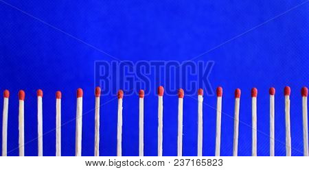 Line Of Seventeen Red Unused Safety Matches On Bright Blue Background With Copy Space For Text. Conc
