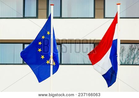 Flags Of The European Union And The Netherlands Against The Background Of A White Wall With Windows.