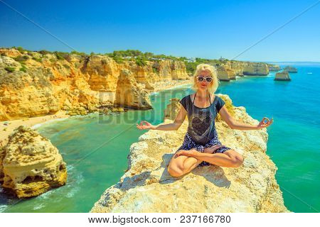 Serene Meditation Yoga. Blonde Tourist Woman Meditating In Lotus Position On Promontory Above Scenic