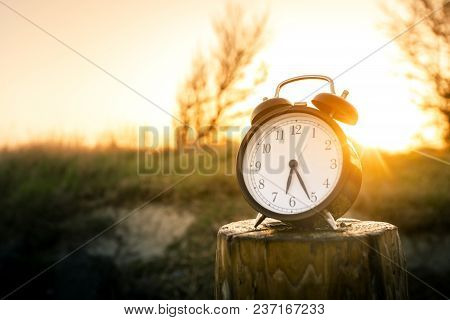 Alarm Clock On A Wooden Post In The Morning Sunrise In A Rural Environment