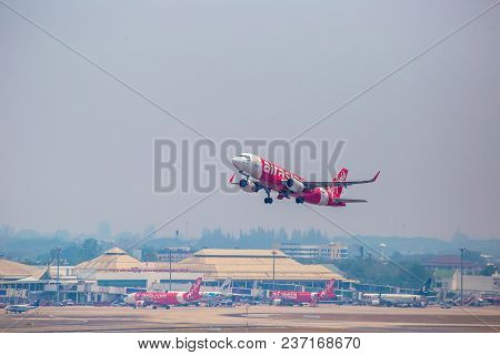 The Red And White Airbus Airplane Of Air Asia (airline Name) Is Flying In The Smokey Blue Sky In Chi