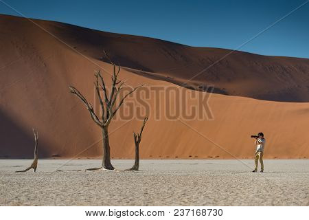 Young Male Photographer And Traveler Taking Photo Of Dead Tree In Deadvlei (sossusvlei) During Sunri