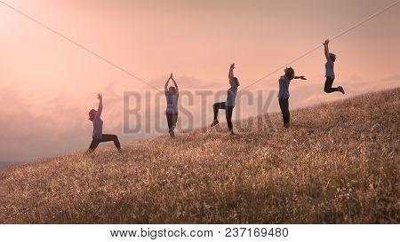 Group Of Same Happy Cheerful Girls Training Yoga Exercise On Idyllic Field At Beautiful Sunny Day Ab