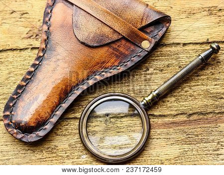 Magnifying Glass Or Loupe On Wooden Table. Top View