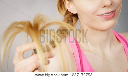 Happy Woman Looking At Her Long Blonde Hair Ends, Seeing Positive Effects Of Using Conditioner. Hair