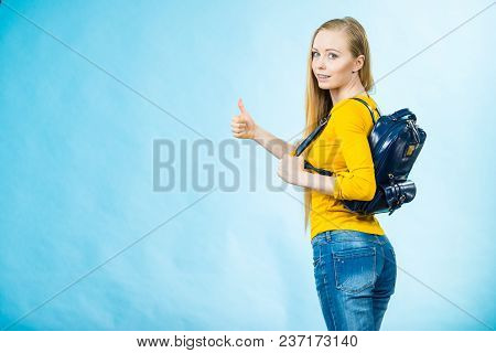 Happy Young Blonde Teenage Girl Going To School Or College Wearing Backpack Showing Thumbs Up On Blu