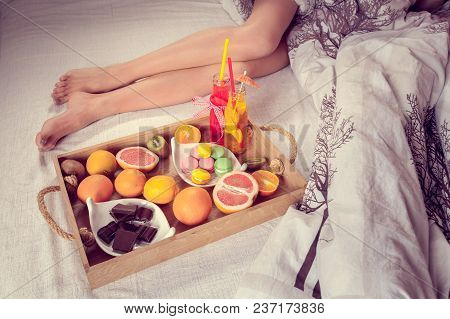 Breakfast From Different Fruits And Beverage To Bed And Female Legs Protruding From Under The Blanke