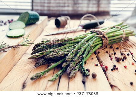 Bunch Of Asparagus With Spices And  Cucumber On A Wooden Background