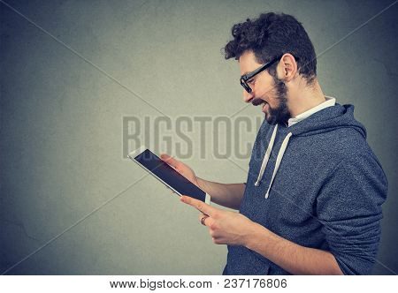 Handsome Young Man Using Tablet Looking At Screen