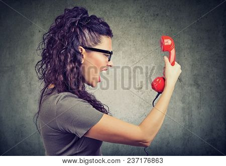 Side View Of Beautiful Woman Holding A Red Telephone Receiver And Yelling In Anger.