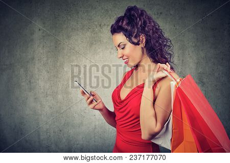 Beautiful Young Woman With Shoppping Bags And Smartphone