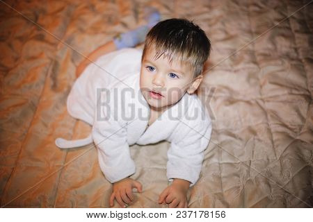 Handsome Boy Lying On The Bed In A Bathrobe