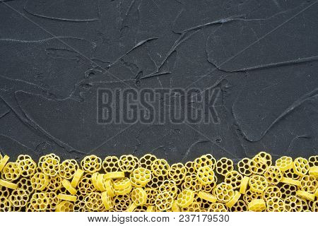 Raw Ruote Beautiful Decomposed Pasta With A Bottom On A Black Textured Background. Close-up View Fro