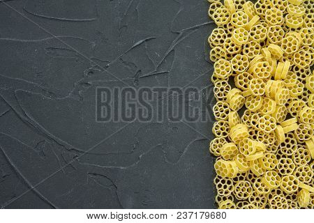 Raw Ruote Beautiful Decomposed Pasta With The Right, On Its Side On A Black Textured Background. Clo