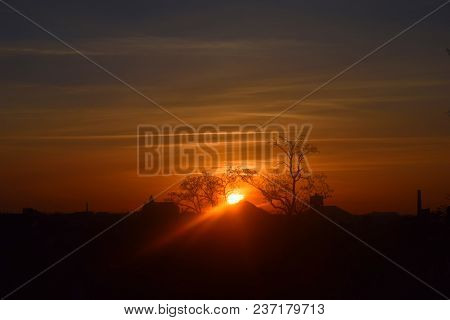 Natural Sunset Sunrise Over Field Or Meadow. Bright Dramatic Sky And Dark Ground. Sunrise. Sun Over