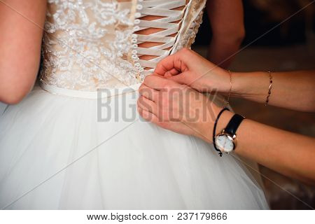 Bridesmaid Hands Fastens Buttons On The Back Of The Bride On The Wedding White Silk Dress With Beige