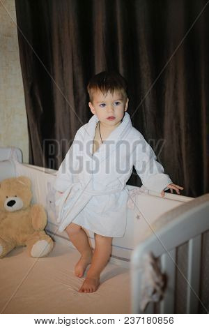 A Beautiful Child Is Standing On The Bed In A Home Bathrobe
