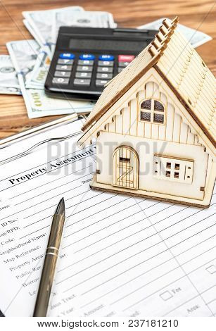 Property Assessment Form With Money, Calculator And Model Of House On The Table. Property Valuation